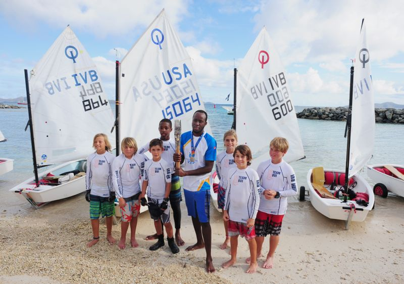 Thad Lettsome (left side of baton); Glenford Gordon (holding baton) and local optimist sailors with the Queen's Baton.